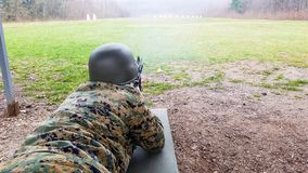 O soldado no departamento militar, com um capacete em sua cabe?a, encontra-se na terra e visa-se o alvo imagens de stock