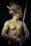 O soldado, o guerreiro com capacete e a espada com seu corpo pintaram o gol Imagens de Stock Royalty Free