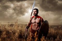 O soldado que vestem na armadura e o loack gostam espartano Foto de Stock