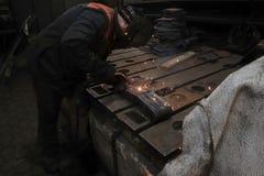 O soldador é contratado em executar o trabalho de solda com a ajuda da soldadura de arco elétrico em seu local de trabalho foto de stock