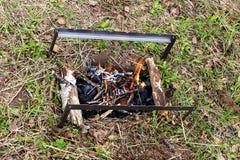 O soldador com madeira ardente do fogo está na grama foto de stock royalty free
