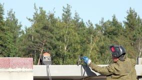 O soldador em uma máscara que está nas escadas e nas tomadas da máquina de soldadura terminal e adiciona a fase às estruturas do  filme