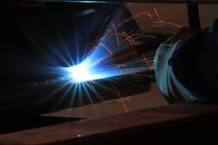 O soldador está soldando a construção de aço com todo o equipamento de segurança Imagens de Stock