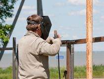 O soldador masculino monta a cerca foto de stock