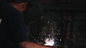 O soldador na máscara protetora faz a soldadura de arco elétrico do metal filme