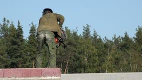O soldador na roupa de trabalho do special no telhado dobra a máquina de soldadura e move-a para o outro partido para a aplicação video estoque