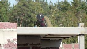 O soldador que trabalha no telhado solda o quadro entre a laje de assoalho nos uniformes de trabalho especiais e máscaras para a  filme