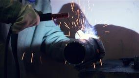 O soldador solda uma tubulação de aço filme