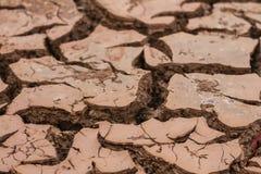 O solo seco e a terra rachada racham profundamente a terra na terra vermelha como um símbolo do clima e da seca quentes fotografia de stock royalty free
