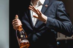 O Sommelier em uma obscuridade - casaco azul que guarda uma garrafa do vinho e diz a audiência sobre os vários vinhos fotos de stock