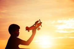 O sonho de uma criança que queira voar em toda parte mostra em silhueta fotos de stock