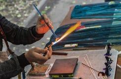 O soprador de vidro faz uma estatueta do vidro Vidro de derretimento em um queimador de gás imagem de stock