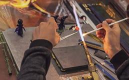 O soprador de vidro faz uma estatueta do vidro Vidro de derretimento em um queimador de gás imagens de stock
