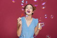 O sopro bonito alegre da jovem mulher bobbles e rir imagem de stock royalty free