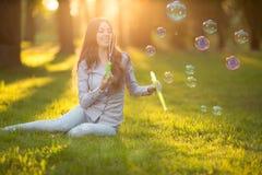 O sopro ocasional da mulher da forma nova da mola borbulha no por do sol dentro Fotografia de Stock Royalty Free