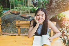 O sorriso adolescente da menina asiática aprecia o livro de leitura foto de stock
