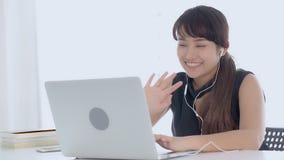 O sorriso asiático novo bonito da mulher diz que olá! usando a rede social do bate-papo com vídeo chamar o laptop video estoque