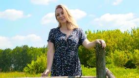 O sorriso atrativo e as namoradeira da mulher aproximam a cerca de madeira Ar livre, grama verde no parque video estoque