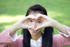 O sorriso bonito adolescente do rosa do vestido da menina do estudante dá o coração Imagem de Stock