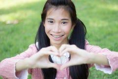 O sorriso bonito adolescente do rosa do vestido da menina do estudante dá o coração Fotografia de Stock Royalty Free