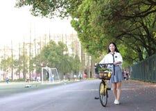 O sorriso chinês da estudante de High School de Ásia da beleza bonita aprecia o tempo livre na bicicleta do passeio do campo de j fotos de stock