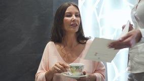 O sorriso e a mulher amigável são de assento e bebendo o chá saboroso filme
