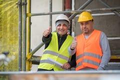 O sorriso e os trabalhadores da construção bem sucedidos que levantam mostrar manuseiam acima do gesto Fotografia de Stock