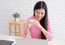 O sorriso fêmea asiático do freelancer e o café da bebida com relaxam o emotio foto de stock