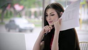 O sorriso feliz da mulher de negócios nova, bom negócio, guarda o assento disponivel dos originais em um café na perspectiva do t filme