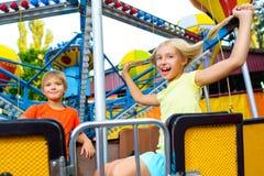 O sorriso feliz pequeno bonito caçoa a montada de um carnaval Fotos de Stock