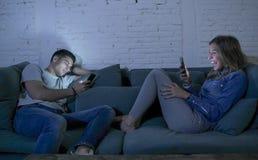 O sorriso novo do sofá do sofá dos pares em casa feliz junto mas separado ignorando-se concentrou-se no telefone celular no Inter foto de stock