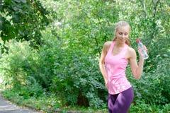 O sportwoman novo atrativo terminou-a dá certo e agora água potável e sorriso no parque com espaço da cópia fotografia de stock royalty free