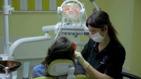 O stomatologist fêmea do doutor no trabalho trata e clarea os dentes ao paciente da jovem mulher na clínica dental médica video estoque