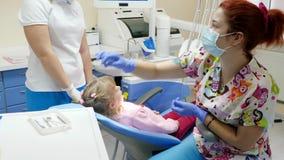 O stomatologist profissional com as ferramentas nas mãos curou os dentes doentes da menina e da ela que dão o gesto positivo dent vídeos de arquivo