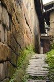 O stree pequeno estende, com parede de pedra e estrada fotografia de stock