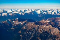 O suíço, Itália e os cumes austríacos com montanha nevado cobrem a vista aérea para o leste durante o voo da tarde imagens de stock