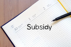 O subsídio escreve no caderno imagens de stock