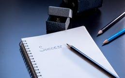 O sucesso é escrito no bloco de notas pequeno Imagens de Stock Royalty Free
