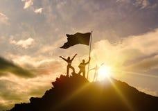O sucesso alto, família três mostra em silhueta, pai da mãe e criança que mantém a bandeira da vitória sobre a montanha, mãos imagem de stock