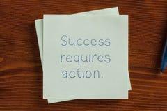 O sucesso exige ação escrita à mão na nota Imagens de Stock