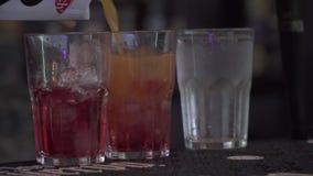 O suco é derramado nos vidros que estão na barra Barman que prepara o close up do cocktail video estoque