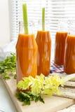O suco de cenoura natural e fresco em umas garrafas pequenas com aipo fresco e centeio liso endurece, centeio do galette Imagens de Stock