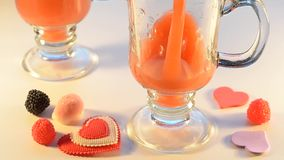 O suco de fruto é derramado em dois vidros, não pode ver a borda Doces e coração decorativo ao redor Foco seletivo vídeos de arquivo