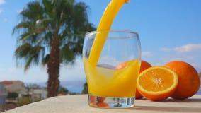 O suco de laranja do close-up derramou em um vidro filme