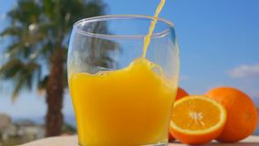 O suco de laranja do close-up derramou em um vidro video estoque