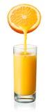O suco de laranja está derramando no vidro Isolado no branco imagem de stock royalty free