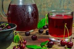 O suco frio da cereja em um vidro e o jarro na tabela de madeira com as bagas maduras na cerâmica rolam Fotos de Stock