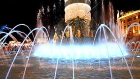 O sumário de Skopje, Macedônia iluminou o fundo da fonte de água de formulários da dança