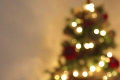 O sumário dourado que pisca a árvore de Natal borrada ilumina o bokeh no fundo morno do ouro, feriado festivo Imagens de Stock