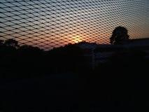O sun& x27; a imagem de s está desaparecendo na parte de trás da construção Nebuloso por um período e com uma malha fotos de stock royalty free